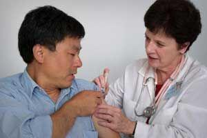 лікар робить щеплення від менінгіту, чоловік дивиться на лікаря